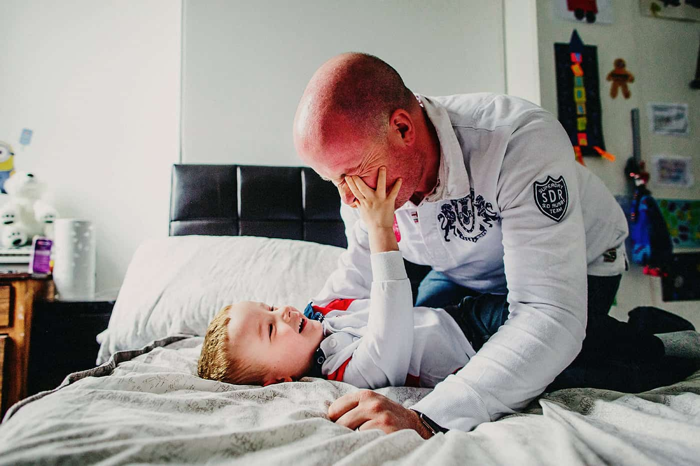 Father and son play together on bed