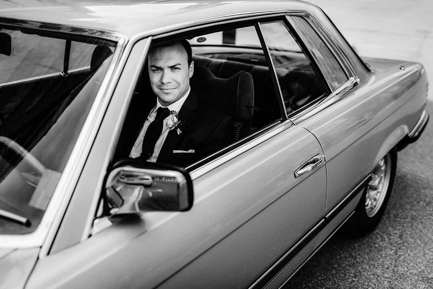 Portrait of a groom in his classic car
