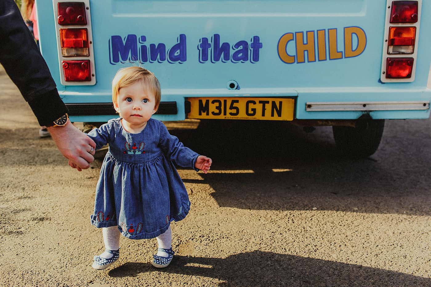 Toddler standing behind ice cream truck with Mind That Child slogan